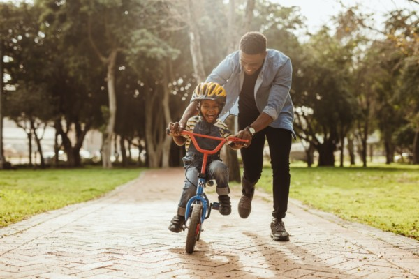 Father teaches his son how to ride a bike without Carpal Tunnel Pain. Carpal Comfort - Designed to Soothe Carpal Tunnel Pain